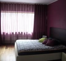 Punakas-lillad kardinad magamistoas.